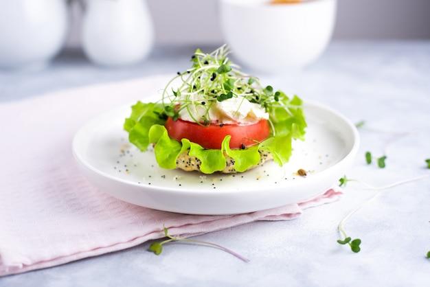 シリアルパンと白いプレートにトマト、レタス、マイクログリーンを添えたベジーバーガー。