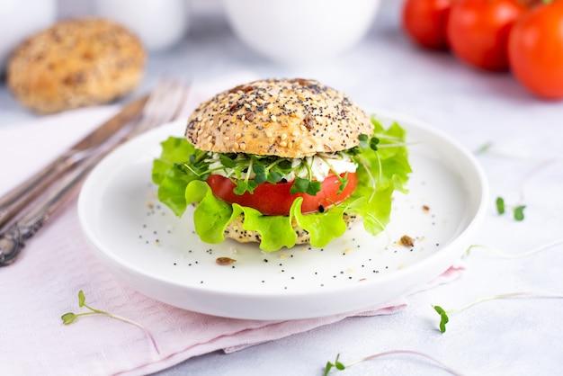 トマト、レタス、マイクログリーンのベジーバーガーとトマト、シリアルパンの白いプレート。