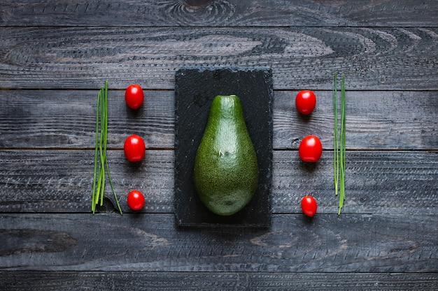 Veggie food composition with half avocado over a darkdish