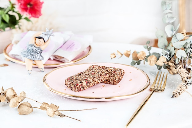Veggie healthy bars with figs served on rose plate above white background. close up horizontal food photo. gluten free, healthy dessert. vegan food and sweets. homemade snack. copy space