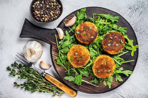 Veggie patty cutlet with lentils, vegetables and arugula. white background. top view.