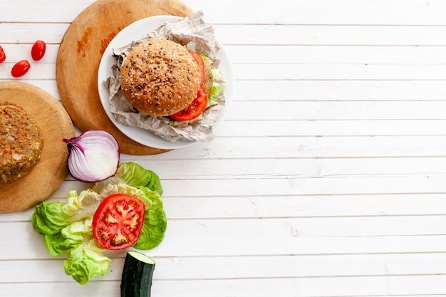 Veggie quinoa burger with  tomato, burger bread, onion, lettuce over wooden white table