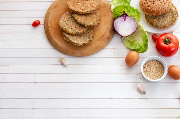 Veggie quinoa burger with  tomato, burger bread, quinoa bowl, onion, lettuce over wooden white background dish with copy space.