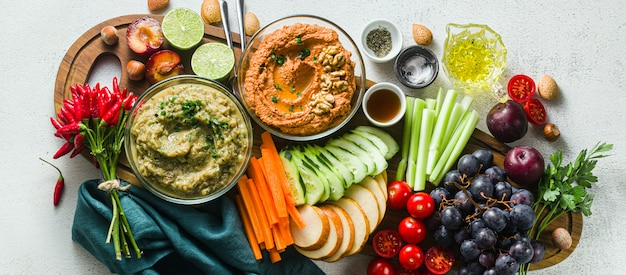 Veggie serving table with snacks with vegetables, fruits, baba ganoush and dip or spread of roasted red pepper and nuts. healthy vegan food for celebration or friends.
