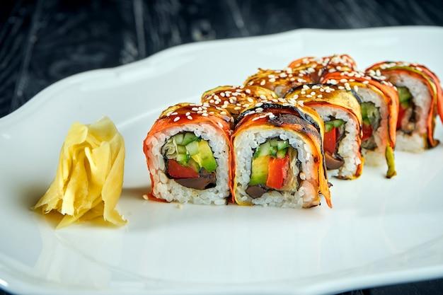Вегетарианский суши-ролл из овощей, моркови, помидоров, огурцов и авокадо, подается в белой тарелке на черной поверхности. японская кухня