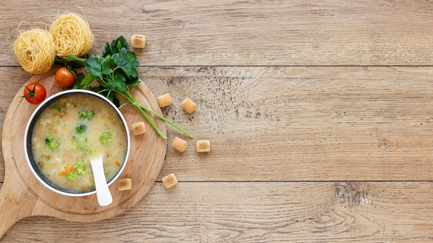 Veggies soup with croutons on wooden board