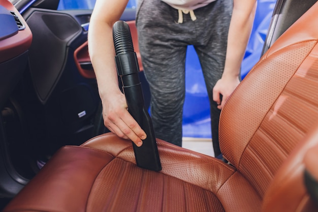 Vehicle interior vacuum cleaning. detail shot of an industrial vacuum cleaner cleaning a car seat.