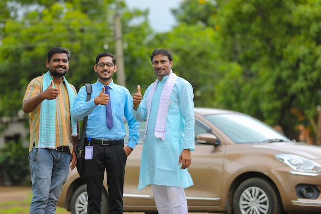 車両ローンのコンセプト:若いインドの銀行家と農民が新しい車を持って立ち、ゴツゴツした音を立てています。