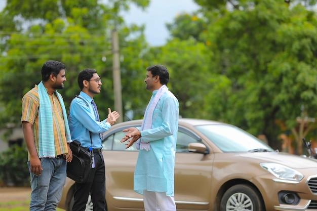 車両ローンの概念:新しい車で立っている若いインドの銀行家と農民