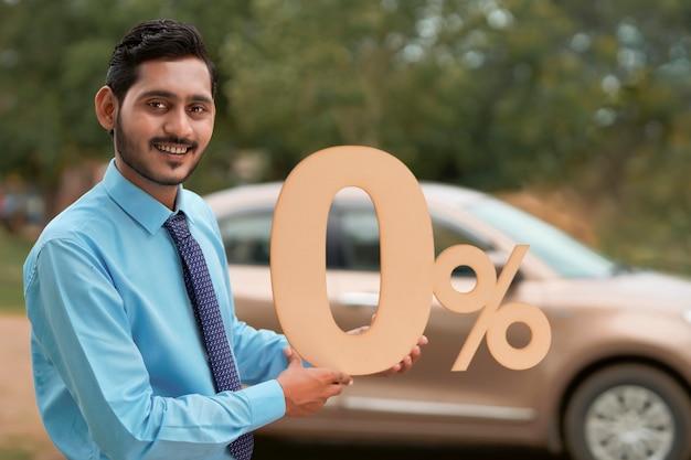 車両ローンの概念:新しい車両にゼロパーセント記号を示す若いインドの銀行家または金融業者