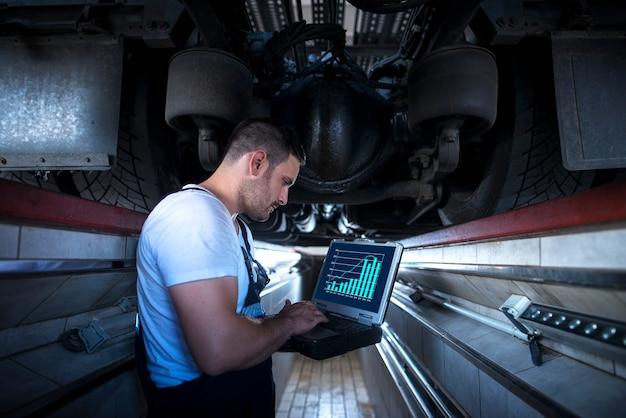 Meccanico del veicolo con laptop strumento diagnostico che lavora sotto il camion in officina
