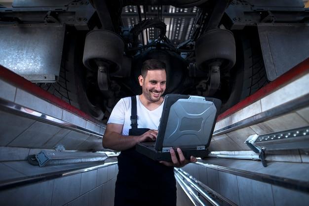Автомеханик с ноутбуком диагностического прибора, работающий под грузовиком в мастерской
