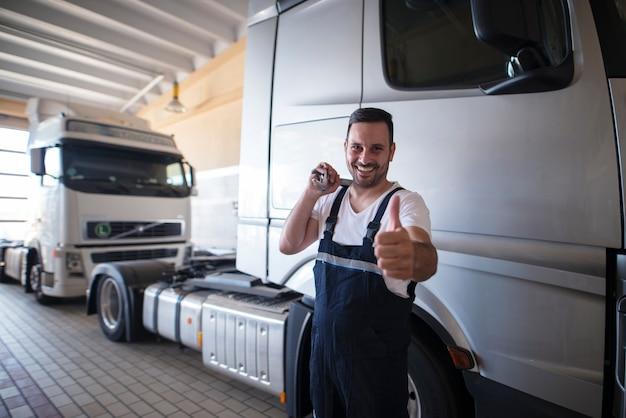 Автомеханик с гаечным ключом и большими пальцами руки стоит перед грузовиками в мастерской