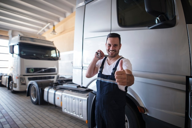 Vehicle mechanic with wrench tool and thumbs up standing in front of trucks in workshop