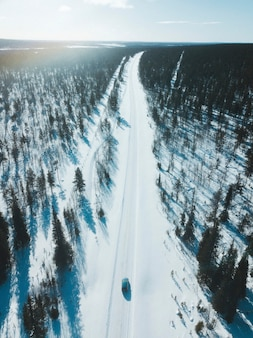 Автомобиль на заснеженной дороге между лесами