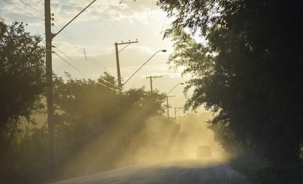 Автомобиль на пыльной дороге с отражениями солнечных лучей