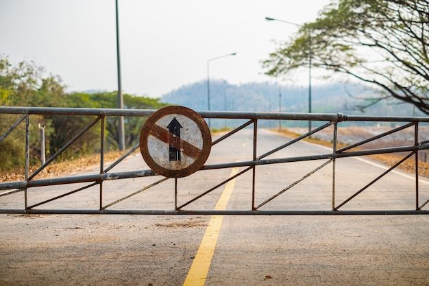 Vehicle security barrier gate and do not go straight direction old traffic sign on the road