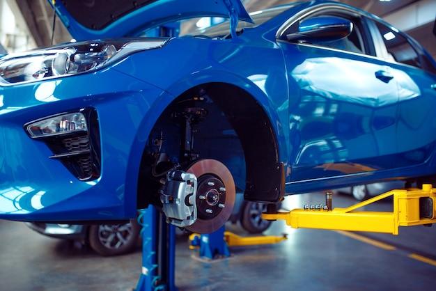 Автомобиль со снятым колесом на подъемнике, автосервис. интерьер автомобильного гаража, оборудование для проверки, диагностики и ремонта