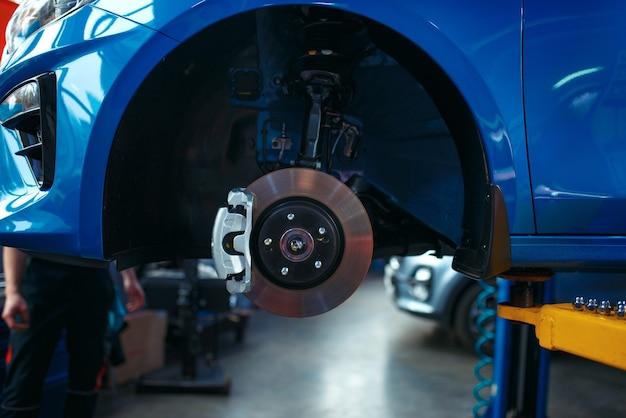 Автомобиль со снятым колесом на подъемнике, автосервис, никто. интерьер автомобильного гаража, оборудование для проверки, диагностики и ремонта.