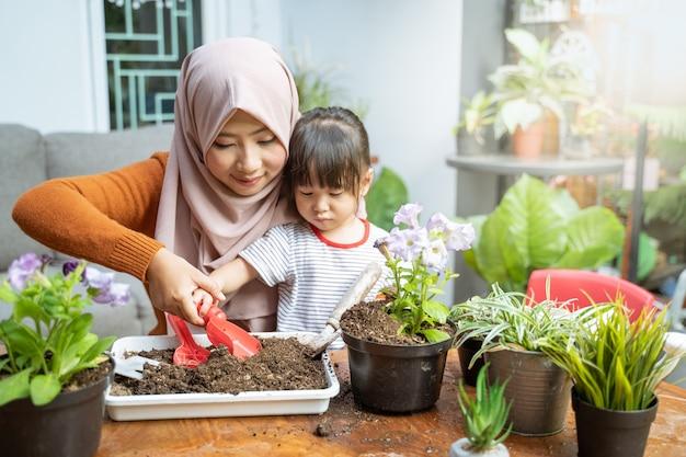 ベールに包まれたアジア人の母親が娘たちが小さなシャベルを持ってトレイから土を取り除くのを手伝う