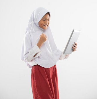 A veiled elementary school girl in uniform stands holding a digital tablet