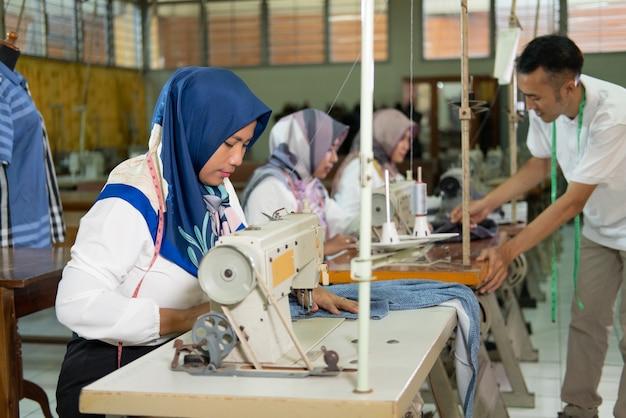 Работницы с вуалью работают на швейных машинах