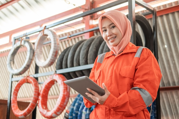 Veiled female mechanic looks at the front while using a digital tablet standing against a tire rack