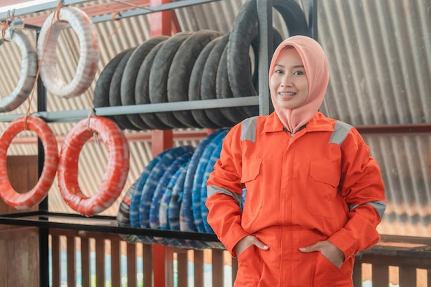 Veiled female mechanic looks at the front with hands in pockets standing against a tire rack