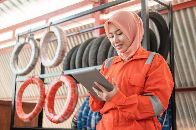 Veiled female mechanic using a digital tablet standing against a tire rack