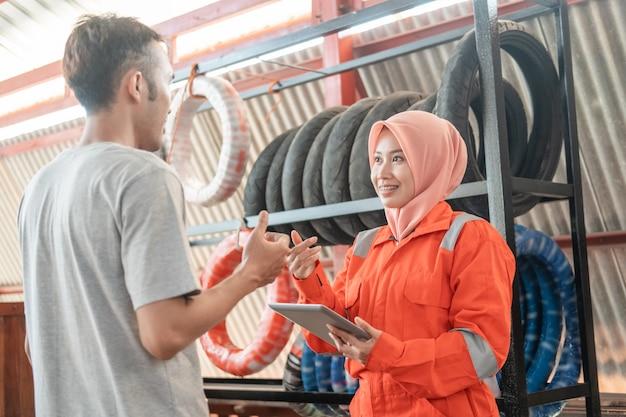 Замаскированные механики-женщины используют цифровые планшеты, болтая с мужчинами-потребителями, стоящими у стойки для шин
