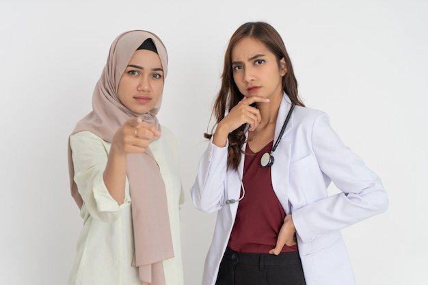 Veiled female patient with pointing gesture and beautiful doctor in white uniform holding chin with ...
