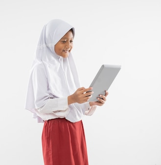 A veiled girl in elementary school uniform stands holding a digital tablet