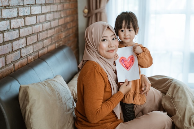 Veiled mother and little girl smile while holding paper with a picture of heart as a symbol of love