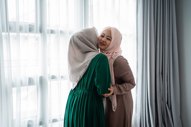 Veiled woman hugs and kiss her sister when meeting
