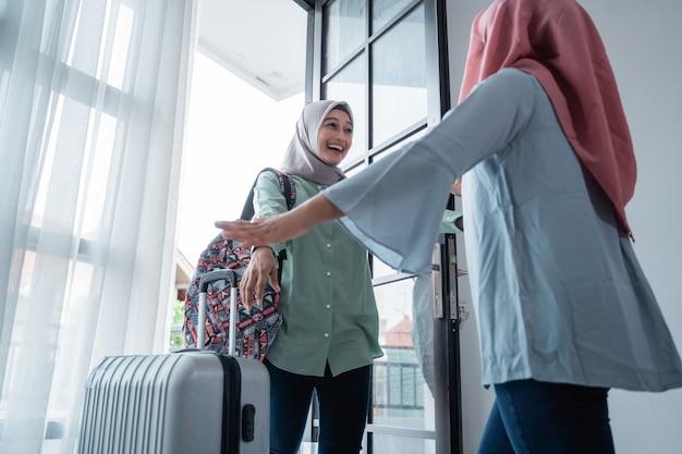 Замаскированная женщина скучает по сестре при встрече у дверей дома