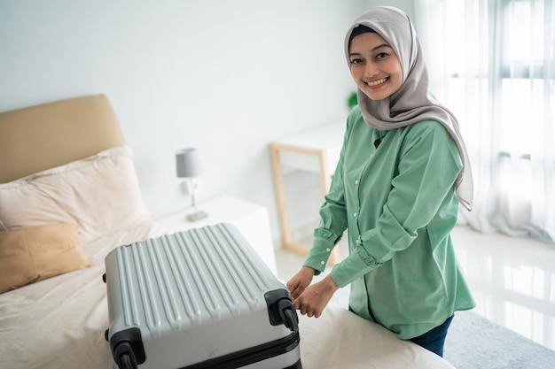 完全なスーツケースを閉じようとしているベールに包まれた女性