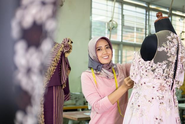 ベールを被った女性のイスラム教徒のファッションデザイナーの女性がドレスを測定するときに笑っている