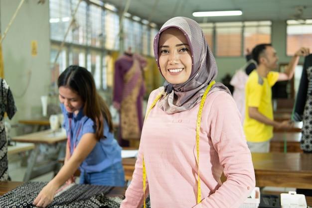 首に巻尺を着用して立っているときに笑顔を仕立てるベールを被った女性