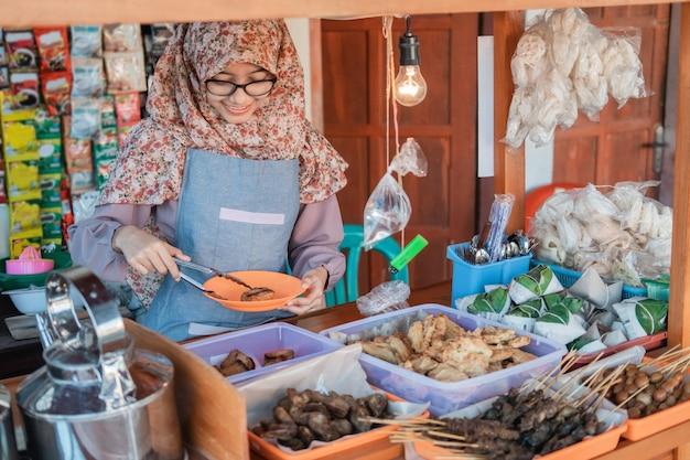 Молодая женщина в вуали, продающая тележку, улыбается, обслуживая клиентов у киоска