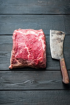 Прозрачный стейк, сырое мясо мраморной говядины, на черном деревянном столе