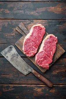Прозрачный стейк, сырое мясо мраморной говядины, на темном деревянном столе, вид сверху