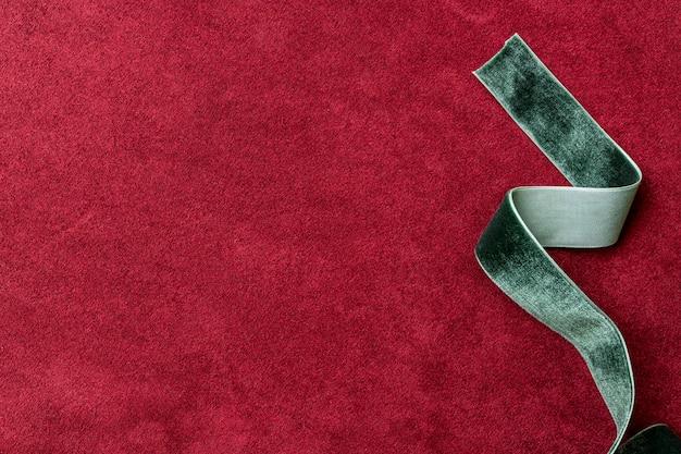 Velvet green ribbon on a red background