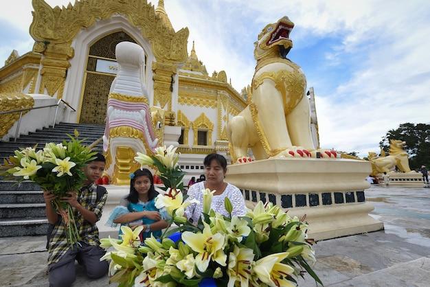 상인과 상인들이 미얀마의 쉐다곤 사원에서 꽃을 팔고 있습니다.