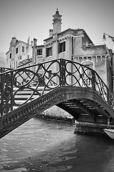 Venetian canal with old cast iron bridge, venice, italy. black and white image