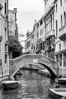 Venetian canal with small bridge, venice, italy. black and white image