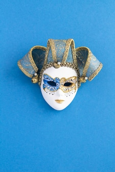 Venetian carnival mask in the center of the blue background. location vertical.top view. copy space.