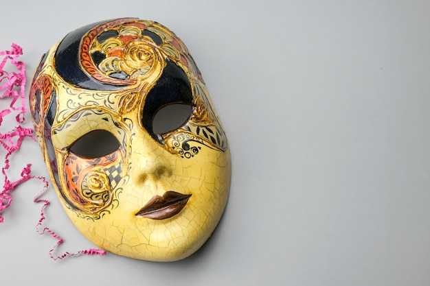 Venetian carnival mask isolated on a grey table