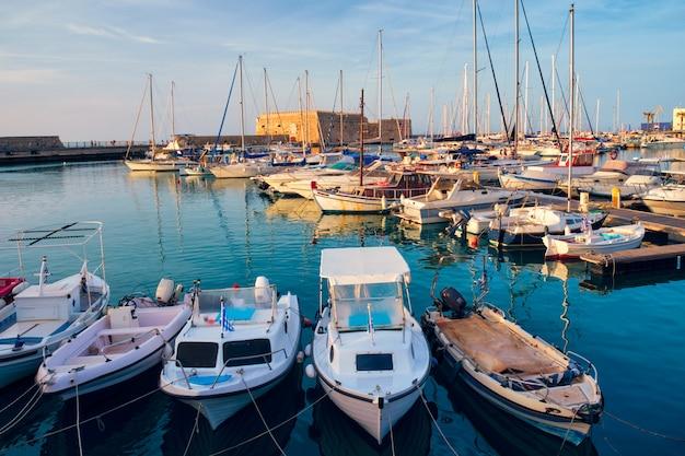 Венецианский форт замок в ираклионе и пришвартованные рыбацкие лодки, остров крит, греция на закате