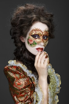 Venetian mask. beautiful woman in vintage dress and a mask on his face.