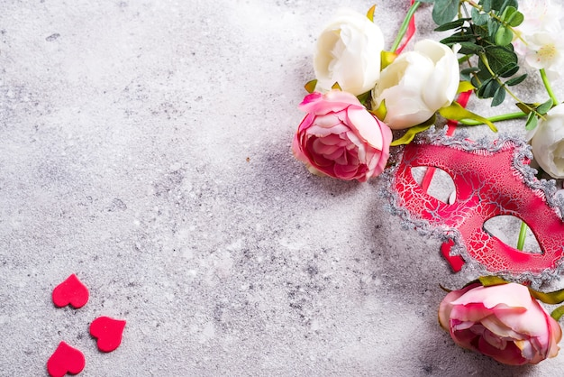 Venetian mask and flowers on stone background. blind date concept, copy space